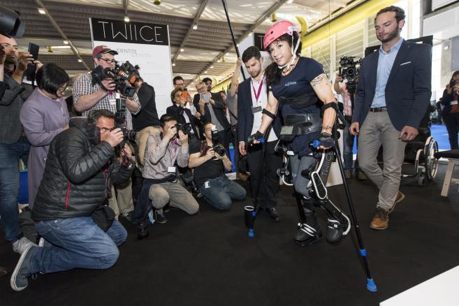 """Silke Pan, niepełnosprawna sportsmenka ścigajaca się na Handbike prezentuje wynalazek o nazwie """"Twiice"""".  Twiice jest egzoszkieletem kończyn dolnych, umożliwiającym osobom z  paraliżem dwukończynowym wstanie, chodzenie a nawet wchodzenie po schodach. Prace nad rozwojem modułowego egzoszkieletu rozpoczęły się w lutym 2015 r. w EPFL (Ecole polytechnique federale de Lausanne). fot. EPA / JEAN-CHRISTOPHE BOTT Dostawca: PAP / EPA."""