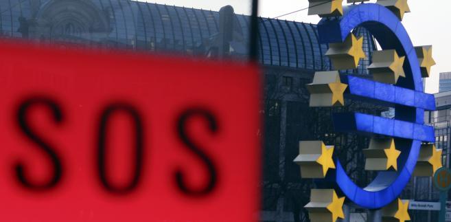 Rzeźba z logo Europejskiego Banku Centralnego ze znakiem SOS w pobliskiej budce telefonicznej we Frankfurcie nad Menem.