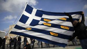 Protestujący Grecy z flagą swojego kraju obklejoną kartkami z napisem na sprzedaż.