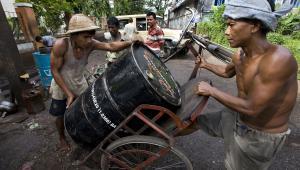Robotnicy transportują baryłkę ropy naftowej na czarnorynkowym straganie w Yangon w Birmie.